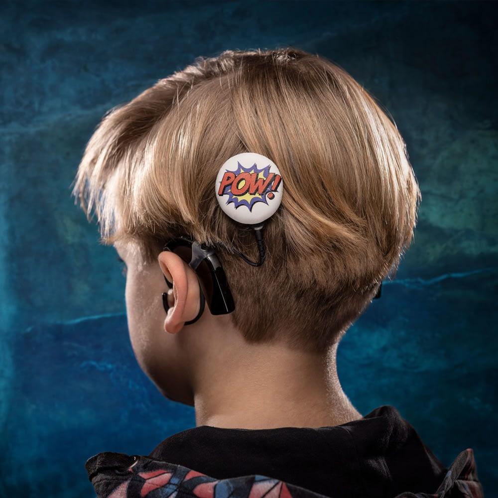 Little boy wearing the pow deesign hearing aid accessory from deafmetal