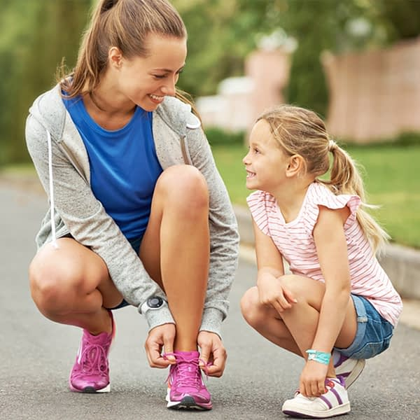 Woman and child going out for a walk tying shoes with the bellman wrist receiver attached
